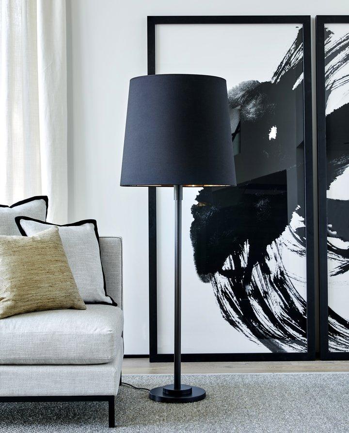 Keaton er en elegant, skulpturell gulvlampe som passer like godt i stua som på soverommet. Lampen er utført i børstet messing og har en luftig lampeskjerm i fin tekstiloverflate som gir et mykt og behagelig lys.